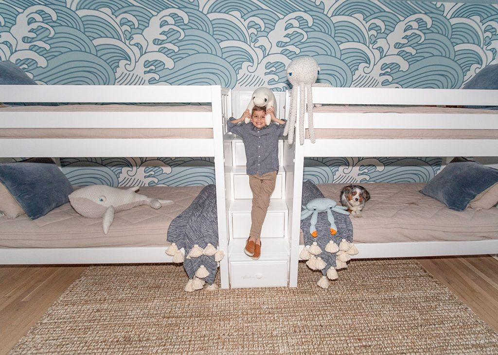 Boy posing with bunk beds in surf themed room