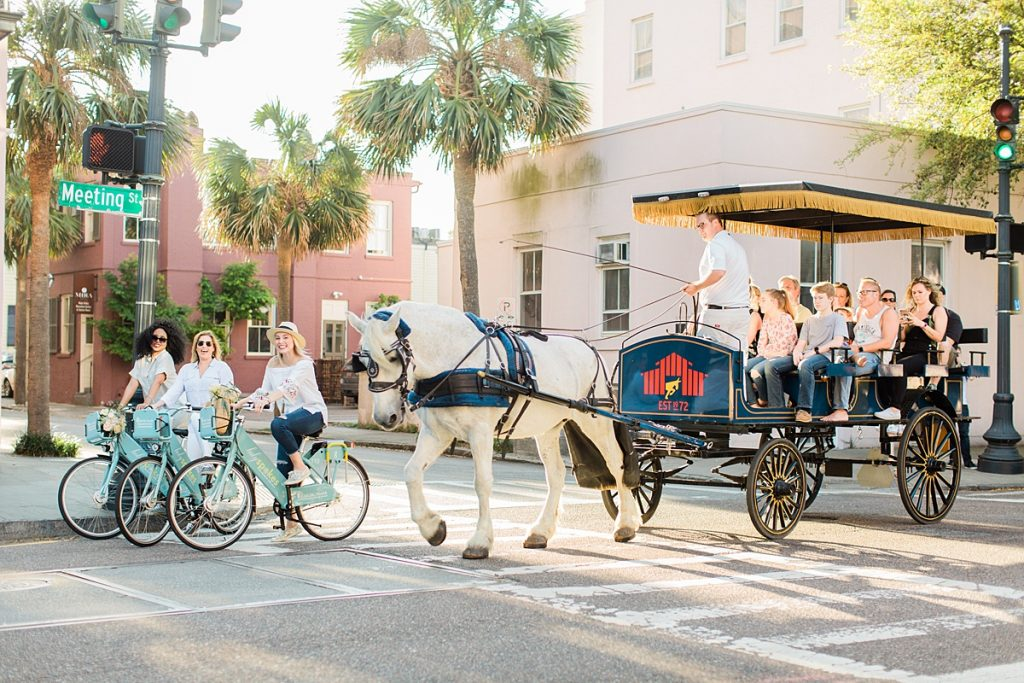Group of girl friends riding bikes next to historic carriage tour through Charleston's historic district