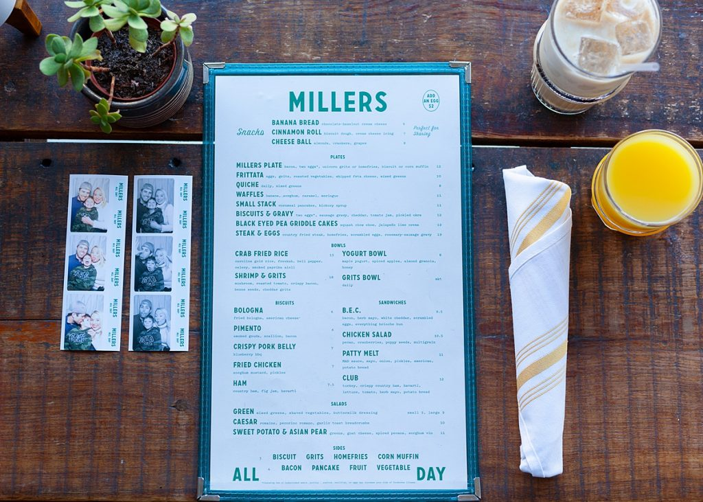 Flatlay of menu, orange juice, silverware, and photobooth strips at Millers All Day restaurant in Charleston