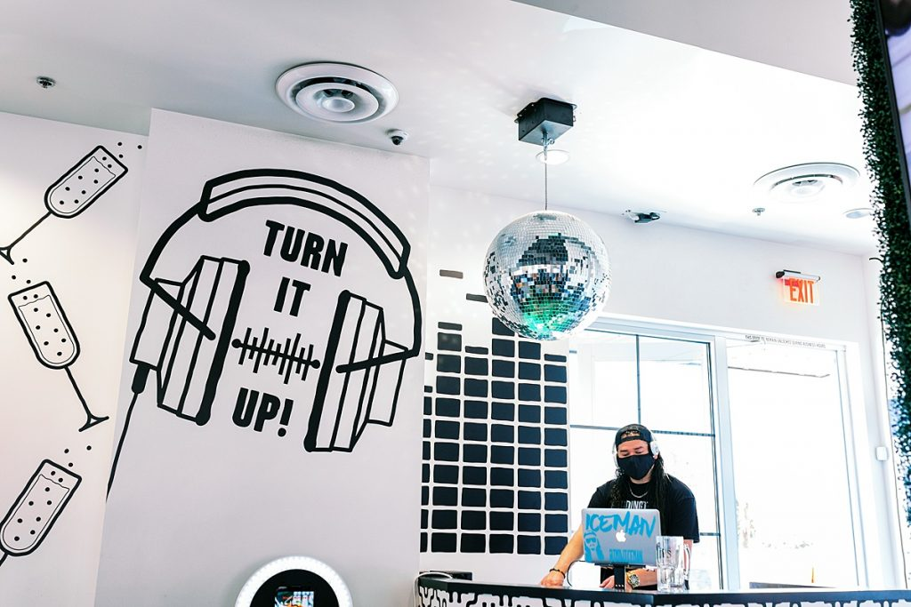 DJ stand at Hash Kitchen restaurant in Phoenix with black graphic wall art