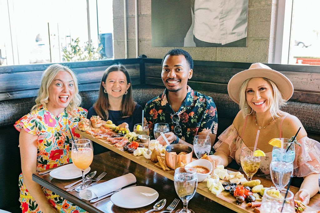Group of friends with 5 foot long charcuterie board at The Sicilian Butcher
